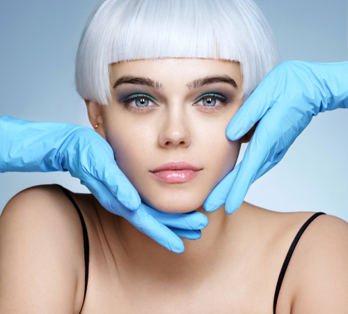 doctors hands in gloves touching face of beautiful woman in blond wig-img-blog